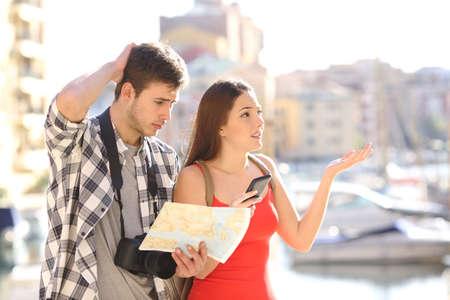 pareja perdida de turistas que buscan ubicación en una guía y el teléfono inteligente con un puerto en el fondo