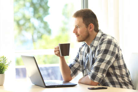 Pensive man with a laptop looking through a window holding a coffee cup at home