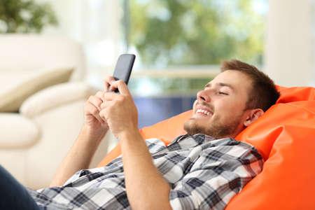Relaxed man using a smart phone lying on an orange pouf in the living room at home with a window in the background