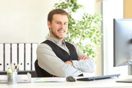 Proud businessman posing sitting in a desktop with crossed arms in his office and looking at you