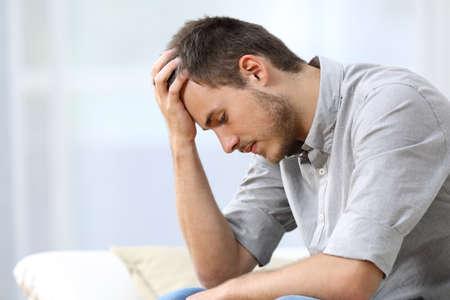arrepentimiento: Vista lateral de un hombre triste con una mano sobre la cabeza sentado en un sofá en la sala de estar en casa