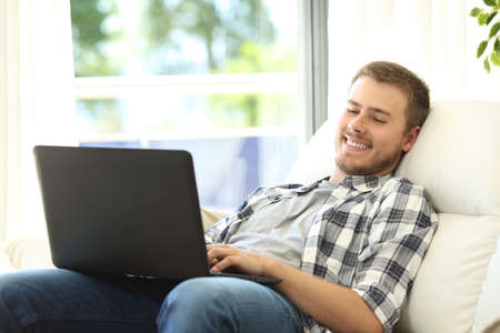 software portability: Relaxed casual man using a laptop sitting on a comfortable sofa in the living room at home Stock Photo