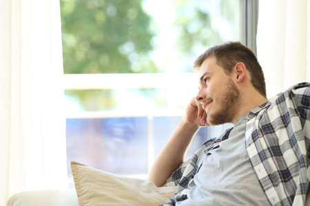 Portrait of a pensive man relaxing sitting on a couch and looking outdoors through a window in the living room at home