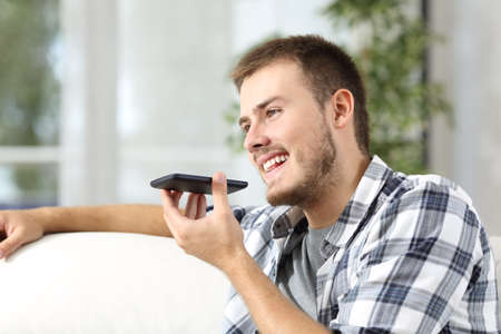 Casual man talking to the mobile phone using the voice recognition at home