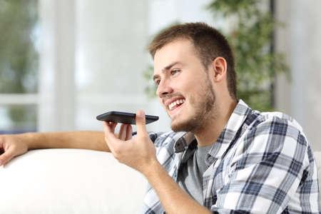 Casual man praten aan de mobiele telefoon met behulp van de spraakherkenning thuis Stockfoto