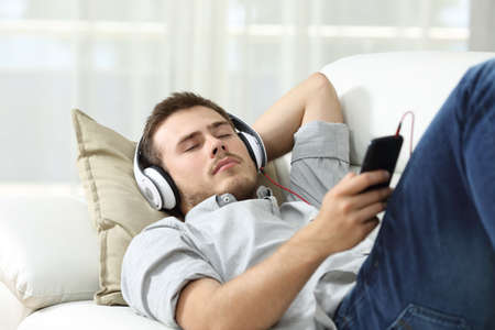slacker: Man sleeping while is listening music lying on a sofa in the living room at home Stock Photo
