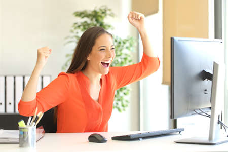 blusa: Emocionado empresario vistiendo una blusa naranja leyendo buenas noticias en línea en un monitor de computadora de escritorio en la oficina Foto de archivo