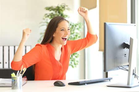 Opgewonden ondernemer met een oranje blouse die goed nieuws online op een desktop computer monitor in het kantoor leest