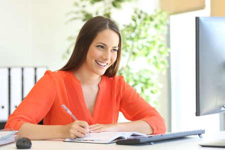 persona escribiendo: la escritura ejecutivo en una agenda y la comprobación de la información en línea con una computadora de escritorio en la oficina