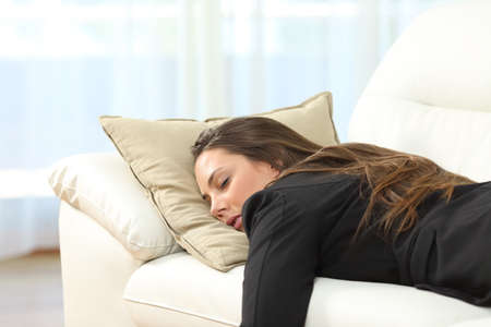 somnolent: Tired executive sleeping lying on a sofa in the living room at home after work Stock Photo