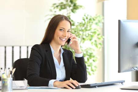 전화로 고객 서비스를 호출하고 사무실의 책상에 앉아 카메라를보고 양복을 입고 행복 경영진의 초상화