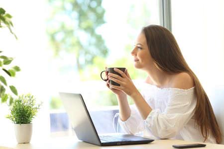 Side view of a pensive housewife with a laptop thinking and holding a coffee cup looking outside through the window of a house interior
