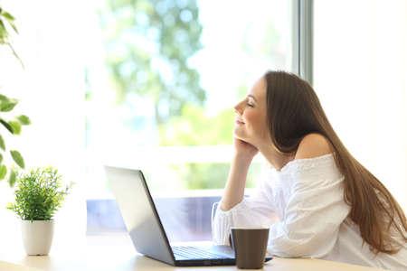 집 인테리어의 창 근처에 앉아 노트북 편안한 행복 한 여자의 측면보기
