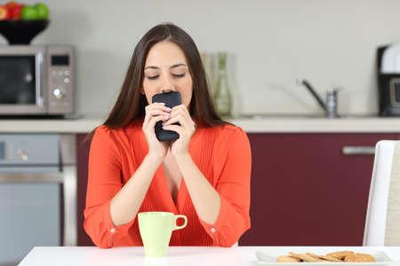 Femme douteuse regardant vers le bas et se demandant si elle doit appeler au téléphone ou attendre un message dans la cuisine au petit déjeuner Banque d'images - 68710803
