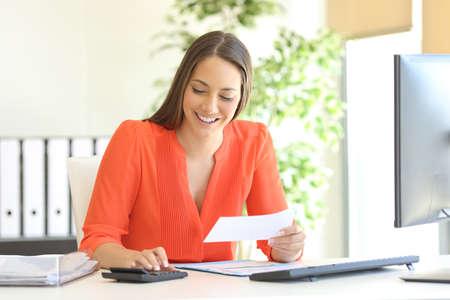 Zakenvrouw die oranje blouse draagt, rekenen en calculeren met een rekenmachine in een bureaublad op kantoor