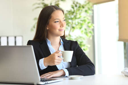 ejecutivo pensativo relajante en un escritorio en la oficina mirando a través de la ventana con una taza de café