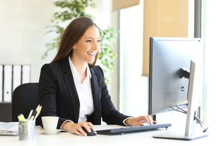 Gelukkige stafmedewerker die met een bureaucomputer op kantoor aan een venster op de achtergrond werkt Stockfoto