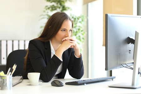 Konzentrierte Geschäftsfrau versucht, eine schwierige Aufgabe auf der Linie in einem Desktop-Computer im Büro zu lösen