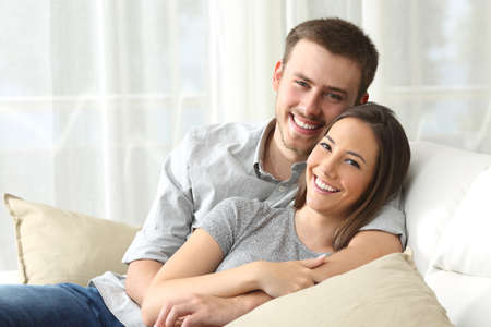 householder: Happy couple sitting in a comfortable couch in the living room and looking at you at home