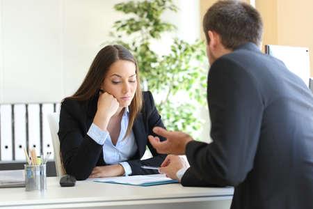 Bad verkoper probeert te overtuigen om een verveelde klant in haar kantoor of zakenman in een sollicitatiegesprek Stockfoto