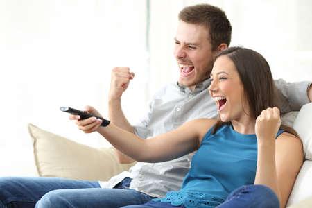 deux Excité regarder la télévision ensemble assis sur un canapé dans le salon à la maison