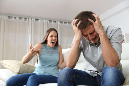 Couple arguing. Wife shouting to her desperate husband sitting on a couch in the living room at home Stok Fotoğraf