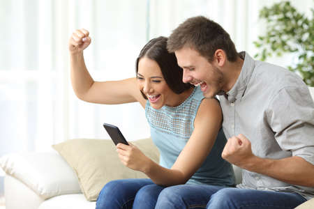 Excited couple watching media content together using a mobile phone sitting on a couch in the living room of a house Фото со стока