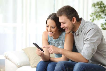 リラックスしたカップルやお友達の自宅のリビング ルームでソファの上に座って汎用携帯電話一緒を使用して