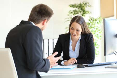 Dependiente talking tratando de convencer a un cliente feliz en un escritorio en la oficina