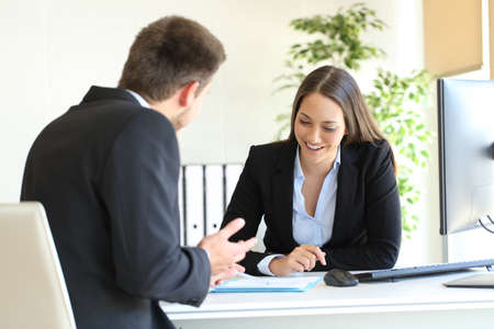 Salesclerk talking trying to convince to a happy client in a desktop at office Stock Photo