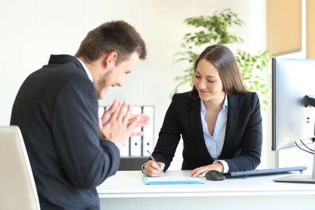 Zakenlui die kostuum dragen die contract na een succesvolle overeenkomst ondertekenen op kantoor