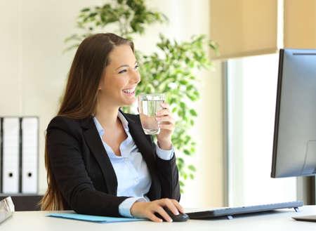 Gelukkige zakenvrouw drinkwater uit een glas en kijkt door het raam op kantoor Stockfoto