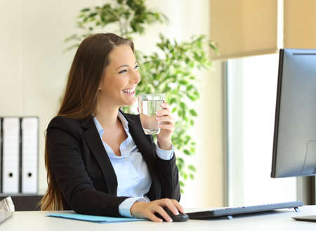 Happy businesswoman drinking water from a glass and looking through the window at office Imagens