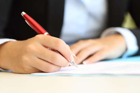 Close up of a businesswoman hands writing in a document on a desktop at office Stock Photo