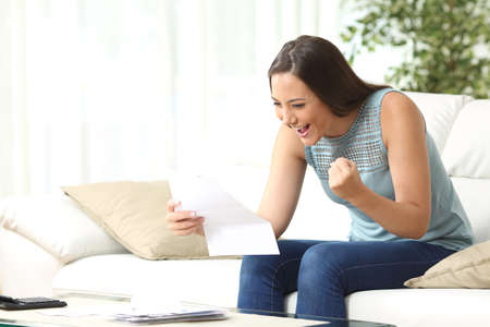 Excited lady reading good news in a paper letter sitting on a couch in the living room at home