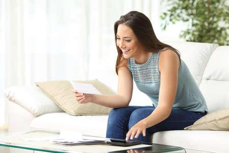 Ménagère calculant la comptabilité tenant un reçu assis sur un canapé dans le salon à la maison Banque d'images - 68711040