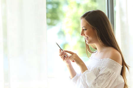 Side view portrait of a casual girl using a smart phone with a warm light near a window of the living room at home