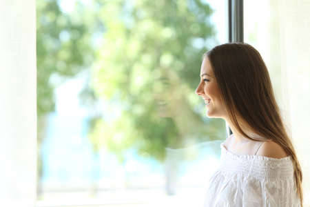 meditation room: Side view of a happy lady at home looking outdoors through a window of a living room or bedroom with a sunny green background