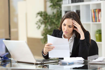 Bezorgd zakenvrouw het lezen van een bericht zittend in een Desktop op kantoor Stockfoto