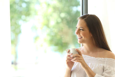 One beautiful girl tasting coffee at home and looking at horizon through a window with a green background outdoors Stock Photo