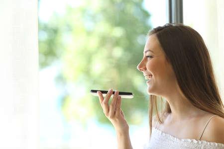 Portret van een meisje die de spraakherkenning van de telefoon gebruikt en door een raam van een huis kijkt