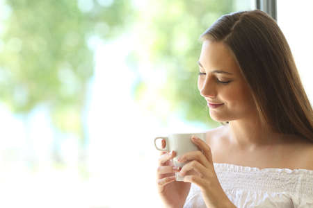 Romantic attractive girl thinking and looking down at coffee cup at home near a window with a natural green background outdoors Stock Photo