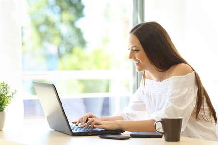 따뜻한 장소에서 녹색 배경을 가진 창문 옆 책상에 앉아 노트북에 쓰는 작가의 측면보기