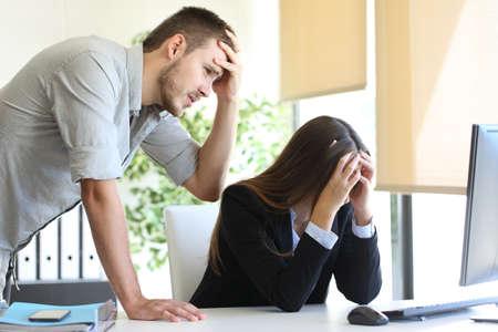 Twee bezorgde collega's met een bureaubladcomputer die een grote fout op kantoor beklagen Stockfoto - 68711049