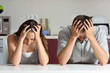 Front view of a sad couple with hands on head sitting in the kitchen of a house Standard-Bild