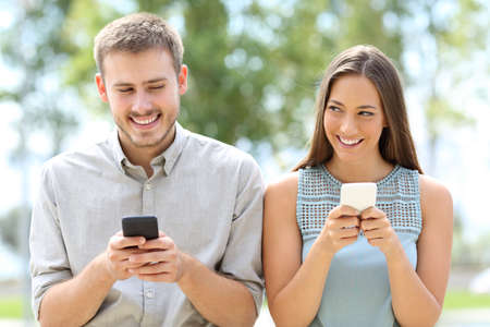 Front view of a couple or friends using smart phones and looking each other askance