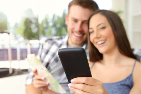 generic location: Couple of tourists searching location in a phone during vacations in an hotel or apartment with a window in the background Stock Photo