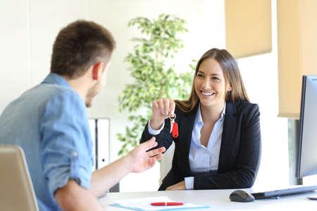 agente de bienes raíces feliz que da claves de la casa a un cliente después de firmar el contrato en la oficina
