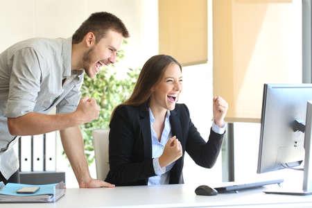 Opgewonden ondernemers co-working kijken naar een desktop computer on line