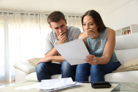 Worried couple reading a letter sitting on a couch in the living room at home Foto de archivo